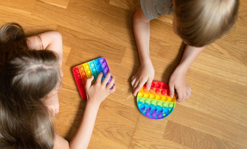 anti stress sensory pop it toys in a children's hands. a little happy kids holding and playing popit